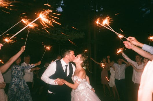 Just married couple kiss as they dance their first dance to Scotland wedding bands with guests holding sparklers in a circle around them.